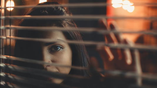 girl face behind small indoor Venetian blinds